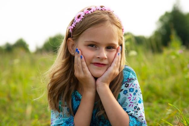 Портрет милой маленькой девочки, лежащей на лугу. красивая девочка 7-9 лет с вьющимися каштановыми волосами.