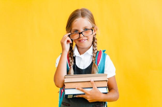 Портрет милой маленькой девочки на желтом фоне. школьница смотрит в камеру,