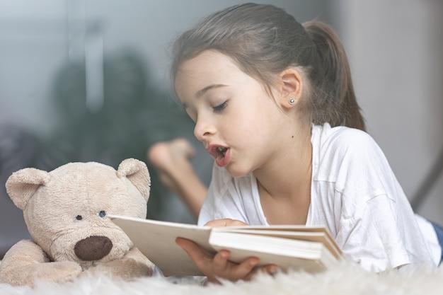 Портрет милой маленькой девочки, читающей книгу дома, лежа на полу со своей любимой игрушкой.