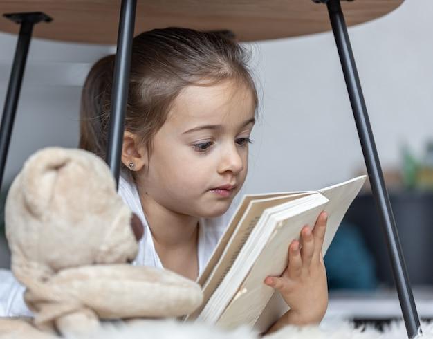 집에서 책을 읽고 있는 귀여운 소녀의 초상화, 그녀가 가장 좋아하는 장난감을 가지고 바닥에 누워 있습니다.