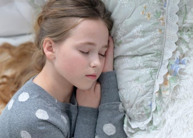 침대에서 자고 있는 귀여운 소녀의 초상화