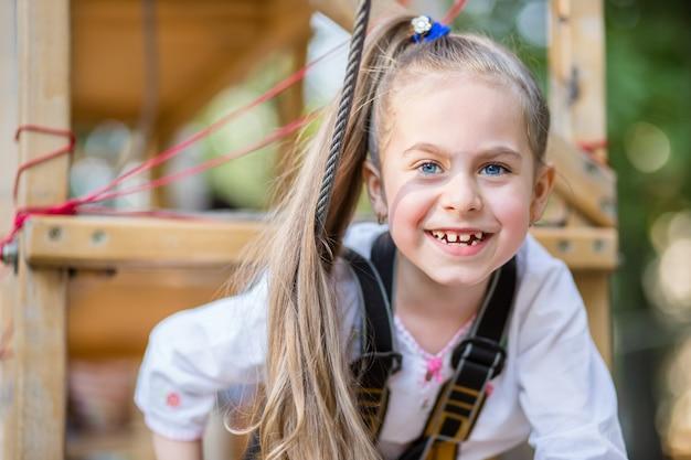 Портрет милая маленькая девочка, которая ходит на веревочный мост в парке приключений канат.