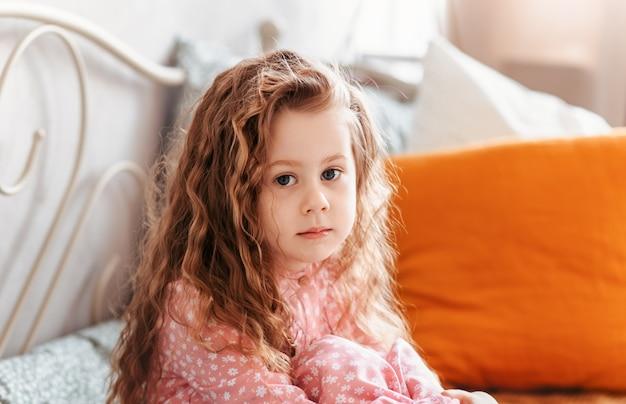 巻き毛のかわいい女の子の肖像画は、カメラをのぞきます