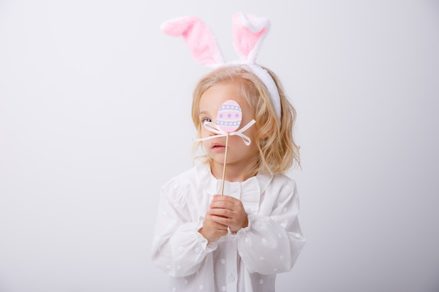 Портрет милой маленькой девочки с ушами кролика на белой предпосылке. христос воскрес