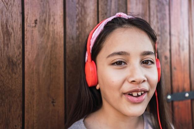 赤いヘッドフォンでかわいい女の子の肖像画。