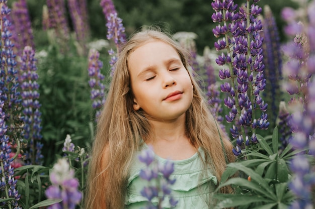 咲くルピナスを楽しむかわいい幸せな少女の肖像画