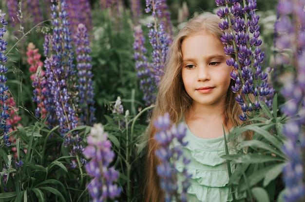 ブルームルピナスとかわいい小さな幸せな女の子の肖像画