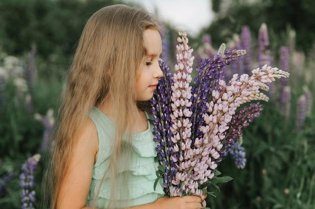 花ルピナスの花束とかわいい小さな幸せな女の子の肖像画