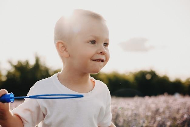 Портрет милого маленького ребенка, играющего в поле цветов с мыльными шарами на фоне заката.