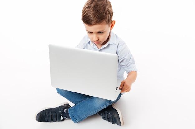 Портрет милый маленький ребенок, используя портативный компьютер