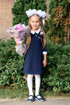 Портрет милой маленькой семилетней первоклассницы с букетом цветов, готовой пойти в школу. обратно в школу концепции