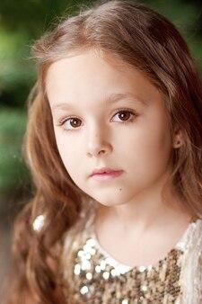 ドレスを着たかわいい長髪の少女の肖像画。写真を閉じる