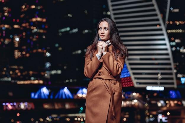 코트와 스카프를 착용하고 밤 모스크바 도시에 대해 포즈를 취하는 귀여운 겸손한 아름다운 소녀의 초상화. 밝은 도시의 불빛