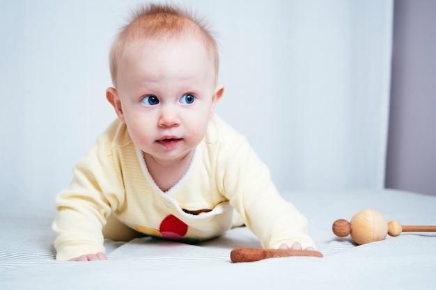 파란 눈을 가진 귀여운 7개월 된 소녀의 초상화. 밝은 방에서 한 아이가 나무 장난감을 가지고 놀고 있습니다. 천연재료로 만든 친환경 어린이장난감.