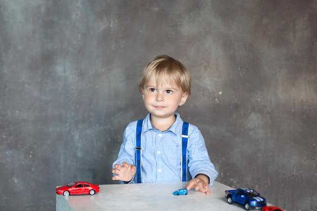 サスペンダー付きシャツを着たかわいい笑顔の小さな男の子の肖像画は、おもちゃのマルチカラーのおもちゃの車で遊んでいます。男の子が幼稚園のテーブルでおもちゃの車で遊ぶ。幼年期の概念