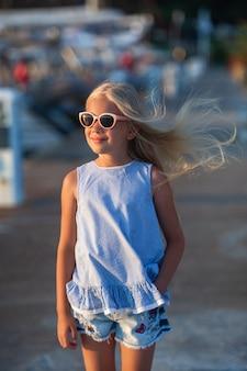 안경을 쓴 귀여운 웃는 어린 소녀의 초상화. 반바지를 입은 소녀와 바다에서 해질녘 파란색 티셔츠. 터키