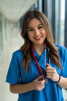 코로나 바이러스 전염병 동안 파란색 제복을 입은 귀여운 웃는 젊은 간호사의 초상화