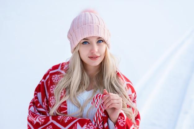 Портрет симпатичной женщины на фоне снега в розовой шляпе и красном пледе позирует на камеру