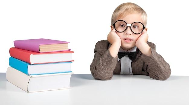 배경에 대해 생각하는 안경을 쓴 귀여운 어린 소년의 초상화