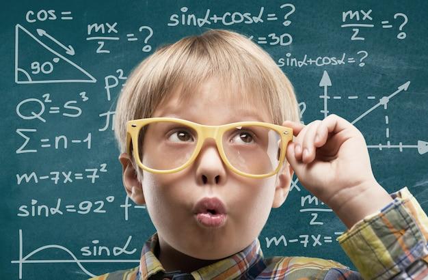 안경 배경에 고립 된 귀여운 어린 소년의 초상화. 스튜디오 촬영.