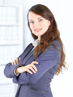 Портрет милой молодой деловой женщины, улыбающейся, в офисной среде