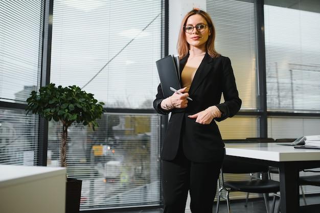 사무실 환경에서 웃 고 귀여운 젊은 비즈니스 여자의 초상화