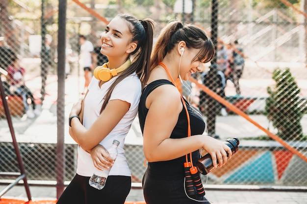 Портрет милой молодой женщины-тренера и ее подруги в спортивном парке делают упражнения для похудения.
