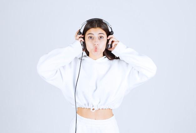 ヘッドフォンで立っているかわいい少女モデルの肖像画。