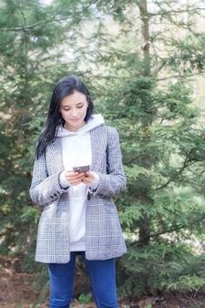 携帯電話を使って美しい春の日に公園で屋外を歩いている格子縞のコートを着たかわいい若い幸せなブルネットのきれいな女性のポートレート。