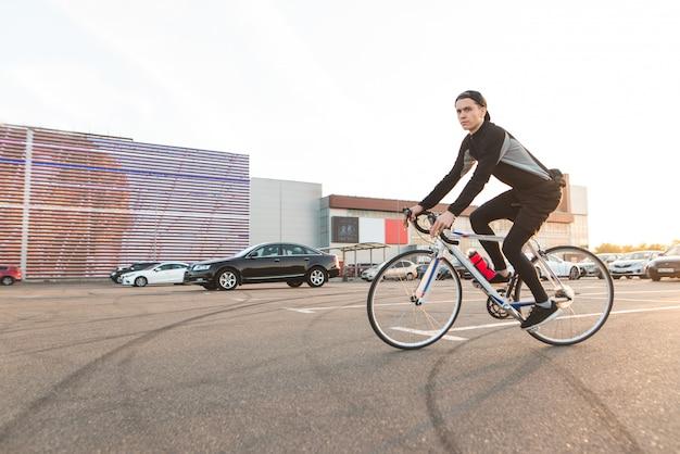 近代建築の背景に駐車場に乗ってかわいい若い男の肖像。