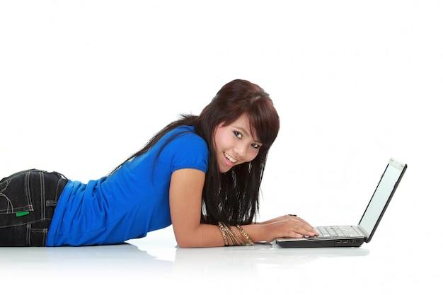 床に取り組んでいるラップトップを使用してかわいい若い女性の肖像画。以上。