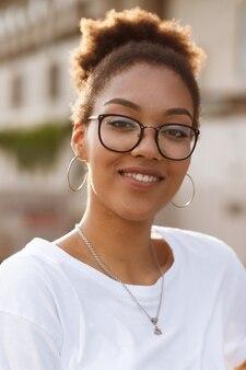 路上で夏に眼鏡の浅黒い肌の少女の肖像画
