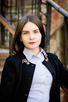 Портрет темноволосой молодой девушки в черной куртке