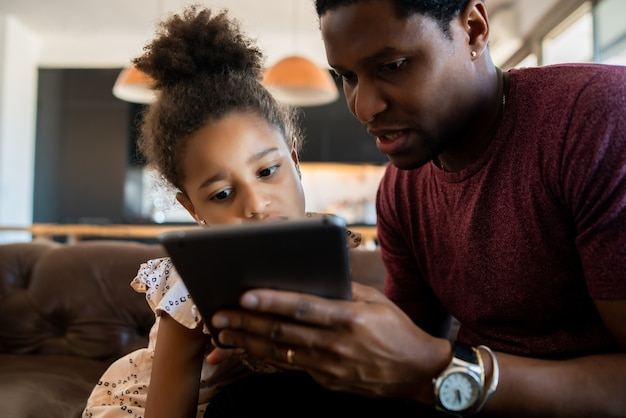 딸과 아버지가 함께 재미와 집에서 디지털 태블릿을 가지고 노는 초상화