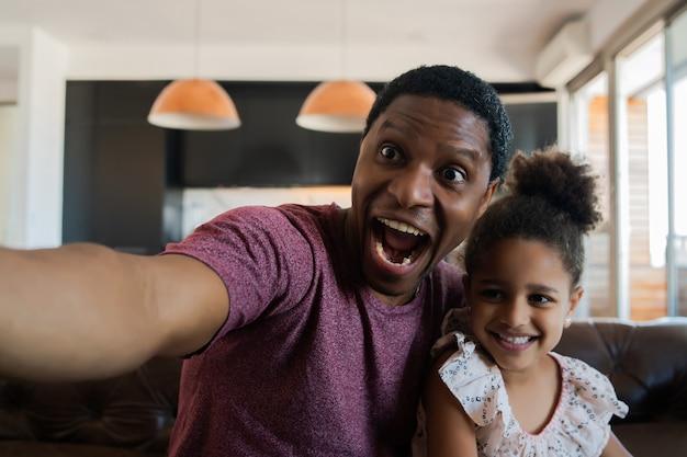 Портрет дочери и отца, весело проводящих время вместе и делающих селфи, сидя на диване у себя дома