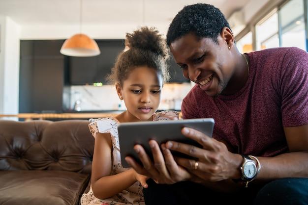 집에 머무는 동안 디지털 태블릿을 사용하는 딸과 아버지의 초상화