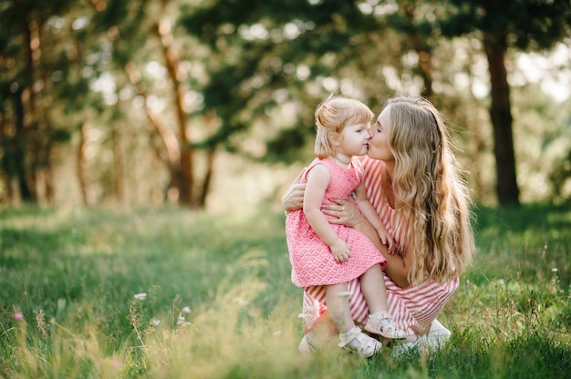 Портрет дочери обнимать и целовать мать на природе на летних каникулах. мама и девочка играют в парке во время заката. понятие дружной семьи. закройте вверх.