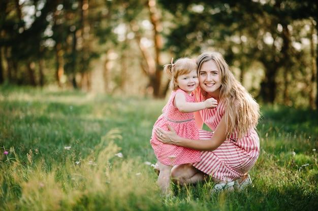 Портрет дочери обнимая мать на природе на летних каникулах. мама и девочка играют в парке во время заката. понятие дружной семьи. закройте вверх.