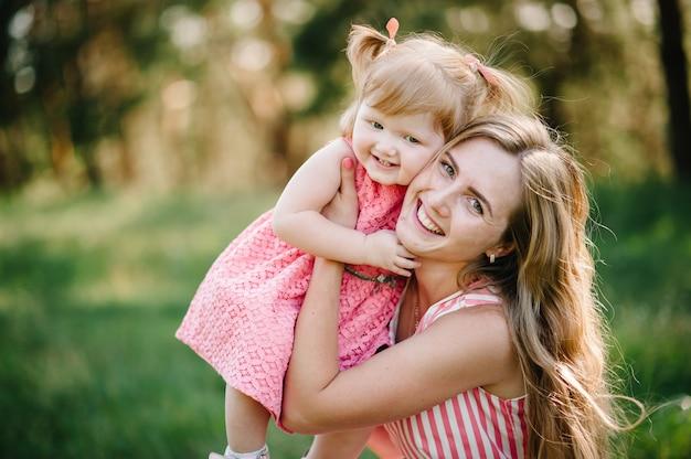 Портрет дочери обнимая мать на природе на летних каникулах. мама и девочка играют в парке во время заката. понятие дружной семьи. закройте вверх. Premium Фотографии