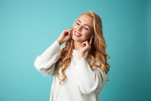 セーターで喜んで若いブロンドの女性の肖像画