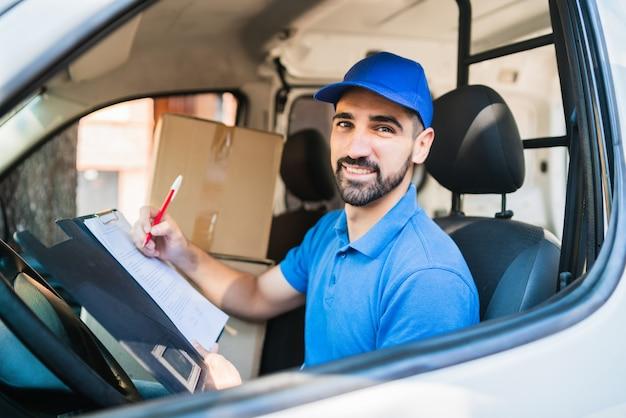 Портрет доставщика, проверяющего список доставки, сидя в фургоне. концепция доставки и отгрузки.