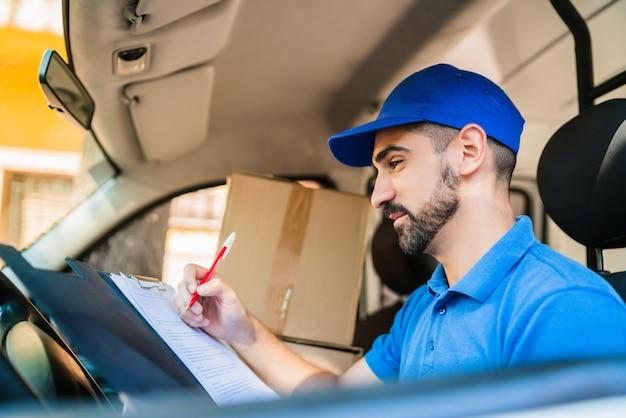 Портрет доставщика, проверяющего список доставки, сидя в фургоне