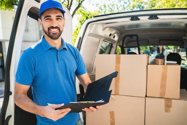 Портрет доставщика, проверяющего продукты в контрольном списке, стоя рядом со своим фургоном