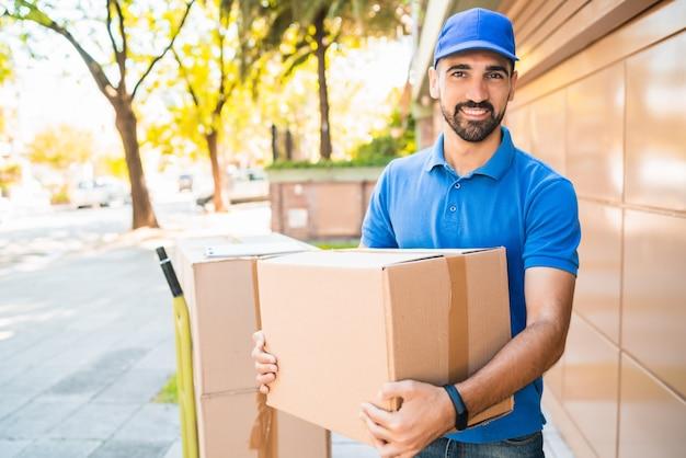 屋外の手に段ボール箱を持つ配達人宅配便の肖像画