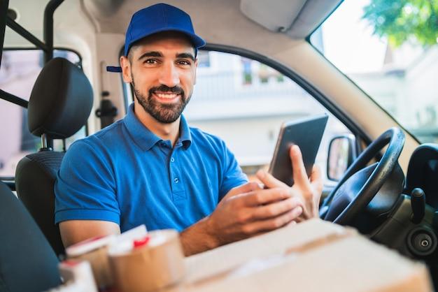 バンに座ってデジタルタブレットを使用して配達人ドライバーの肖像画。配送サービスと配送のコンセプト。