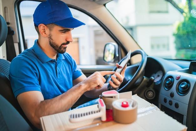 バンに座ってデジタルタブレットを使用して配達人ドライバーの肖像画