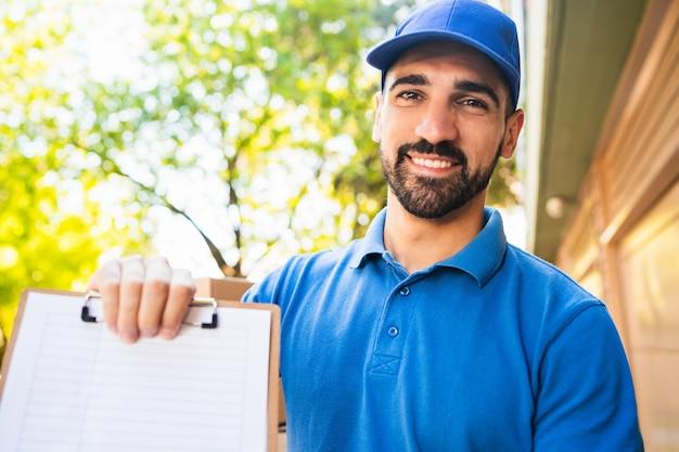 Портрет доставщика, давая буфер обмена клиенту для подписи. концепция доставки и отгрузки.