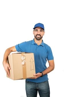 白い壁に段ボール箱を保持している配達人の肖像画。配送と配送のコンセプト。