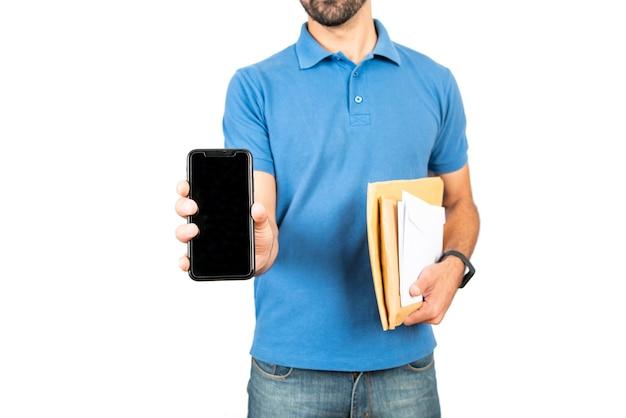 패키지를 들고 흰색 바탕에 휴대 전화를 보여주는 배달 남자의 초상화. 배달 서비스 및 배송 개념.