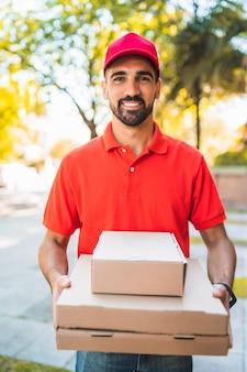 通りの屋外で段ボールのピザの箱を持つ配達人の肖像画。配送と配送サービスのコンセプト。